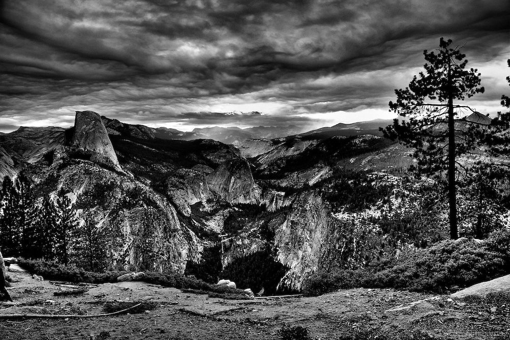 Storm clouds hang over little Yosemite Valley and the Mist Trail. Halfdome, Libert Cap, Nevada Falls and Vernal Falls are visible from Washburn point along Glacier Point Road. Yosemite National Park, Sierra Nevada Mountains, California
