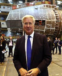 ALTERNATE CROP Defence Secretary Michael Fallon speaks to media in front of HMS Audacious at BAE Systems, Burrow-in-Furness, where he will attend a steel-cutting ceremony to formally commence production of the UK's next generation of nuclear submarines.