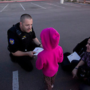 A Phoenix police officer talks with a child as a CPS caseworker looks on. CPS was taking custody of the children.
