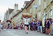 Annual Woolsack Race locals race through town carrying sacks of wool to prove strength, in Tetbury, The Cotswolds, Gloucestershire, UK