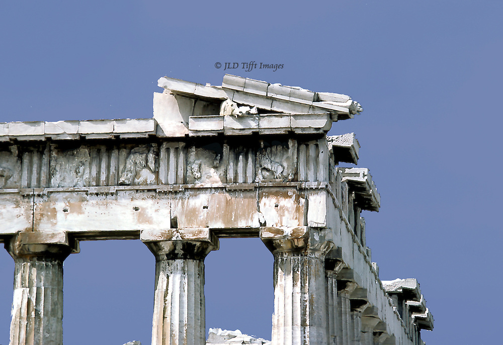 Acropolis: Parthenon, details of entablature.  Doric column capitals, abaci, entablature, and a corner of the cornice with horse's head silhouetted against blue sky..