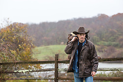 rugged cowboy working on a ranch in the rain
