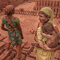 Brick field workers in the factory near Dhaka, Bangladesh.<br /> <br /> In the brickfields, labour is largely hired through a traditional system of recruitment operative through contractors. They collects workers for the brickfields from remote villages and also many times climate migrants come to the city and choose brick factories as their first job. Most of the workers come with their families and live near the site.
