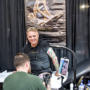 Ben Carter, Tattoo a client at The Great British Tattoo Show, on 26 May 2019, London, UK.