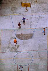 Youths play basketball on a rundown court in Havana, Cuba. (Photo © Jock Fistick)