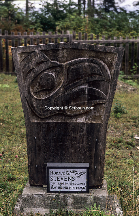 Canada. Queen Charlotte islands. Skidegate cemetery, Village of the Indians  - Haidas -  on queen Charlotte island    Canada  /  cimetière de Skidegate, village des indiens  - Haida -  sur l(île de la reine Charlotte.    Canada   /  Cimetière de Skidegate. Monument funéraire en granité en forme de Grand Cuivre orné d'un corbeau gravé en bas-relief. La partie inférieure de son bec est décorée d'un labret.   /      L3296  /  R00314  /  P108737 +