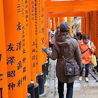 A woman walks down one of the paths covered in orange gates at the Fushimi Inari Taisha shrine in Kyoto, Japan.
