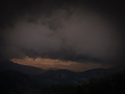 warm light at the end of day shows through under a heavy dark cloud layer with ridges silhouetted in warm light in the Tahoma State Forest of the Cascade Range of Washington state, USA