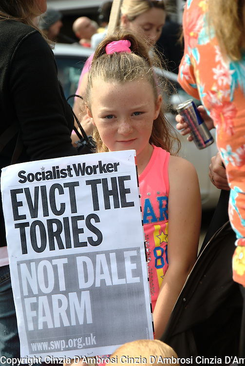 A young girl holds a sign. Among the 90 families set to lose their homes at Dale Farm, many are children.