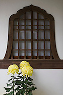 Japanese Window with chrysanthemums.  Japanese traditional architecture makes use of shapes, contours, and spaces to create an effect that is purely Japanese.  Windows play an important part as the indoor/outdoor motif is usually a part of the overall style.