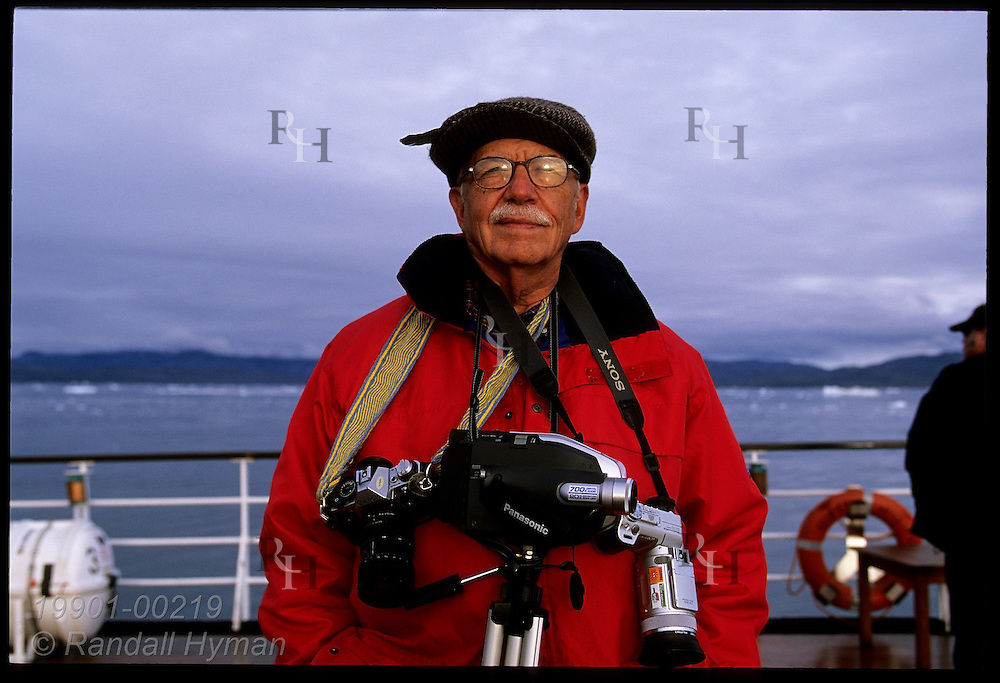Cameras and tripod hang from passenger's neck as he surveys Disko Bay atop the Clipper Adventurer cruise ship; Greenland