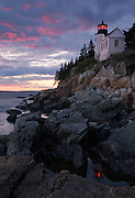 The picturesque Bass Harbour lighthouse is juxtapositioned again a colorful sky and reflections of the lighthouse in a seawater pool, Acadia National Park, Maine, USA
