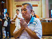 27 JANUARY 2017 - BANGKOK, THAILAND: A man prays at Wat Mangkon Kamalawat on Chinese New Year in Bangkok. 2017 is the Year of the Rooster in the Chinese zodiac. This year's Lunar New Year festivities in Bangkok were toned down because many people are still mourning the death Bhumibol Adulyadej, the Late King of Thailand, who died on Oct 13, 2016. Chinese New Year is widely celebrated in Thailand, because ethnic Chinese are about 15% of the Thai population.      PHOTO BY JACK KURTZ
