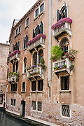 Flowers on old balconies along a canal in Venice. Venezia, founded in the 400s AD, is capital of Italy's Veneto region, named for the ancient Veneti people from the 900s BC. The romantic City of Canals stretches across 100+ small islands in the marshy Venetian Lagoon along the Adriatic Sea, between the mouths of the Po and Piave Rivers. The Republic of Venice was a major maritime power during the Middle Ages and Renaissance, a staging area for the Crusades, and a major center of art and commerce (silk, grain and spice trade) from the 1200s to 1600s. The wealthy legacy of Venice stands today in a rich architecture combining Gothic, Byzantine, and Arab styles. Venice and the Venetian Lagoon are honored on UNESCO's World Heritage List.