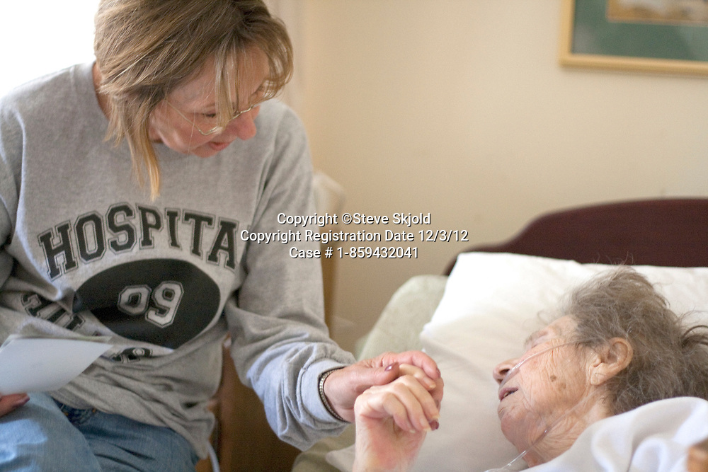 Daughter comforting mom in hospital after falling in her assisted living complex age 64 and 95. Fergus Falls Minnesota MN USA