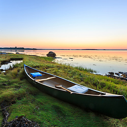 A canoe at sunrise on Lanes Island in Casco Bay. Yarmouth, Maine.