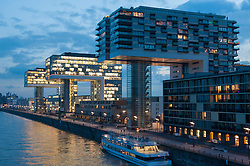 Evening view of modern cranehouses at Rheinauhafen mixed residential and commercial property development beside River Rhine in Cologne Germany