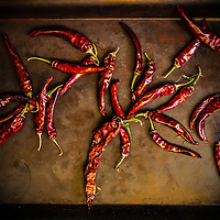 Thai cayenne peppers drying on a black metal tray.