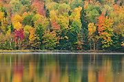 Intense fall color lines and reflects on Franklin Falls Pond in the Adirondack Mountains of New York.