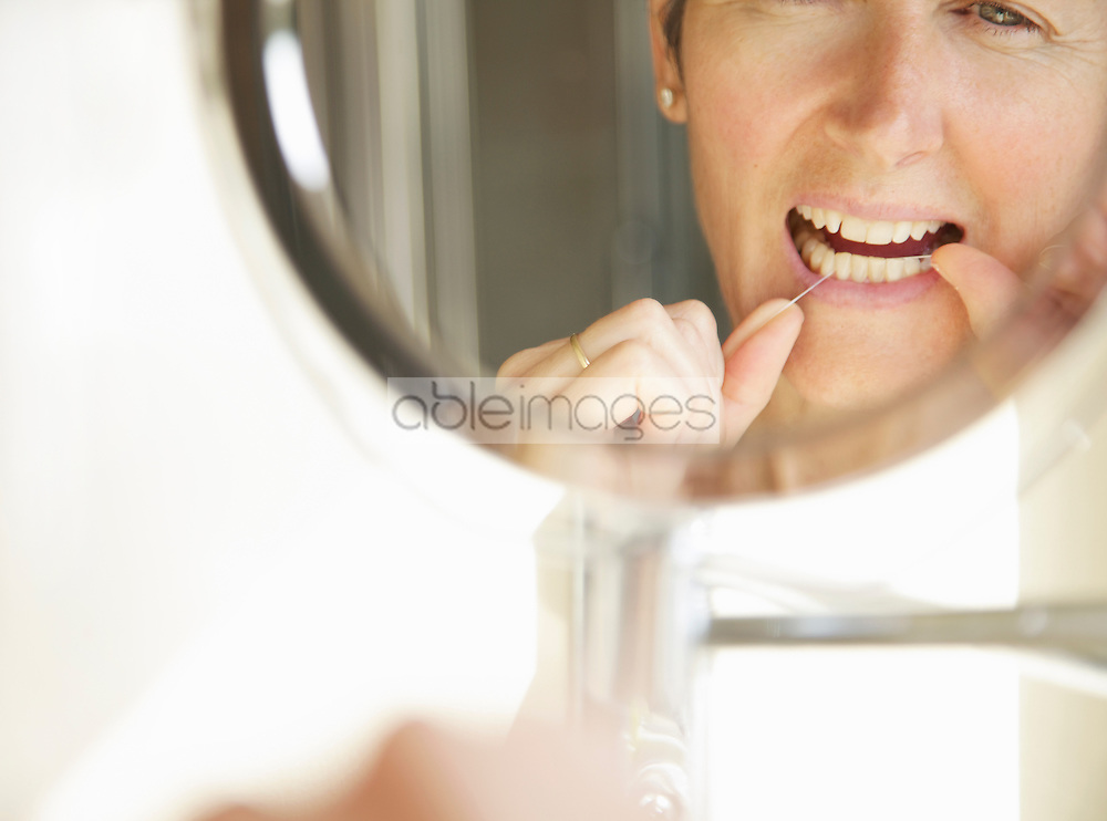 Woman Looking into Round Mirror Flossing Teeth