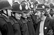 Picket wearing a joke police helmet talking to Police at Orgreave 1984-85 miners strike. © Martin Jenkinson