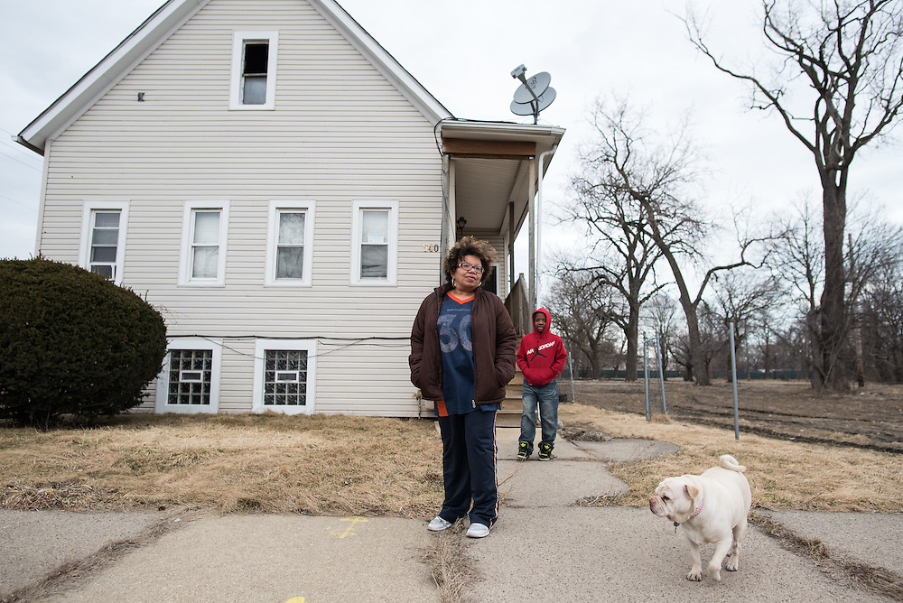 Margaret Bonett and one of her grandsons Malik and dog Roxie stand in front of their family house on a mostly deserted block in Chicago's Englewood community. Since 2011, Norfolk Southern Railway has been buying out and demolishing houses in Bonett's neighborhood to make way for a rail yard expansion project and as of March 2016, Bonnet's family was one of three home owners who refuses to sell.