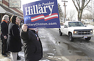 A man holds up a campaign sign before Hillary Clinton arrives for a campaign stop at the Fair River Oaks Council (FROC) office in Dayton, Thursday, February 14, 2008.