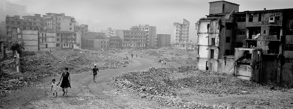 Inhabitants of Gaoyang walking by the razed buildings of the old city. Positionned by a subsidiary of the Yangtze, the city will be flooded in the summer of 2006.
