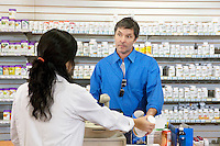 Mature man buying pills from female employee in drugstore