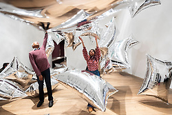 © Licensed to London News Pictures. 10/03/2020. Gallery staff interact with an installation artwork titled Silver Clouds, 1994, by artist Andy Warhol at an exhibition showing at the Tate Modern. London, UK. Photo credit: Ray Tang/LNP