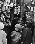 Robert F Kennedy (1925-1968) Democratic Senator for New York, right centre,  and Donald F Benjamin. center, of the Central Brooklyn Coordinating Council, join children at playground children outside a building, 5 February 1966. 'World Telegram & Sun' photograph  by Dick DeMarsico.
