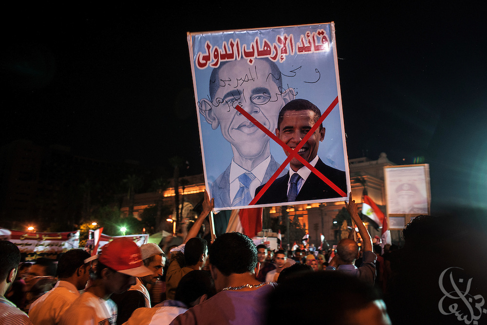 """Egyptians holding an anti-Barack Obama poster take part in mass demonstrations called for by Gen. Abdel Fattah El Sissi, the head of Egypt's military, in the Tahrir Square area of downtown Cairo Egypt on Friday July 26, 2013. EL Sissi had asked Egyptians to take to the streets on Friday to show the world that he had a mandate to deal with """"violence and terrorism""""."""