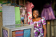 Ojiugi proudly shows off what she learnt on the Youth for Technology training about the importance of eye-catching displays to attract people into the shop.<br /> <br /> Ojiugi Ogbuji started her business in 2000, beginning with door to door sales of baby items. <br /> <br /> She later expanded into the unit next door and started selling soft drinks and water too. <br /> <br /> She attended the Youth for Technology business training first and then heard about the business advice SMS service.