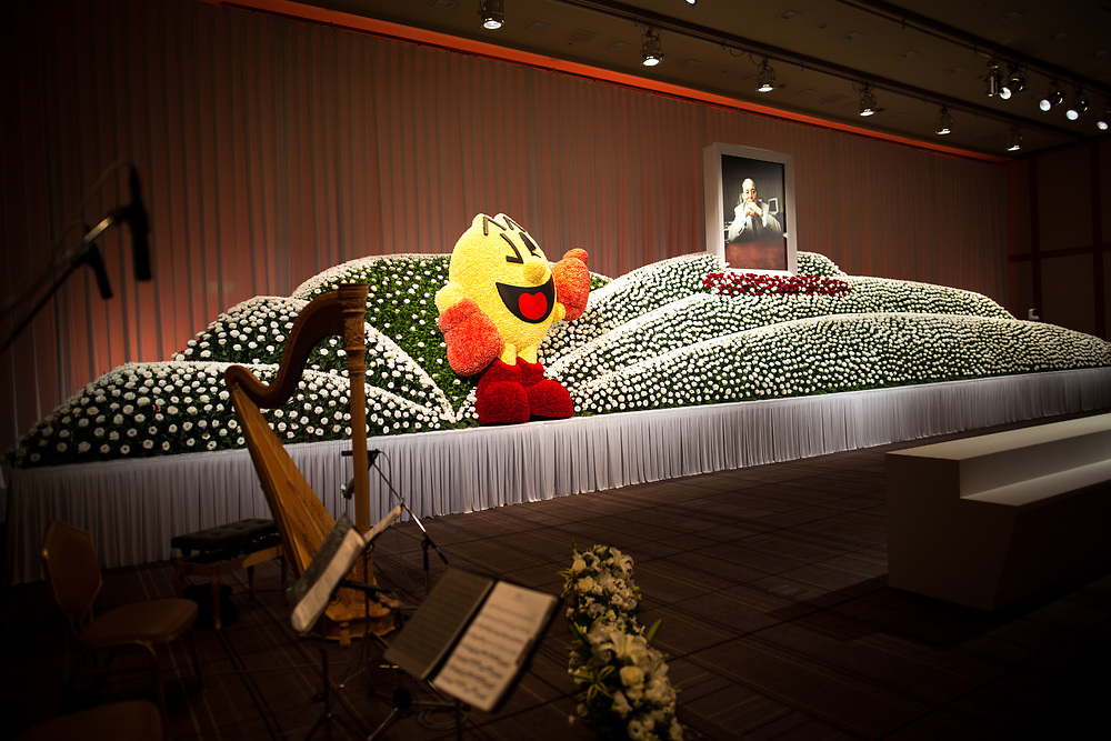 "TOKYO, JAPAN - MARCH 21 : Flowers surround a portrait to commemorate the late Masaya Nakamura, The founder of video game company Bandai Namco and known as the ""father"" of Pac-Man during the memorial ceremony in Tokyo, Japan on March 21, 2017. (Photo by Richard Atrero de Guzman ANADOLU Agency)"