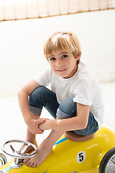 Portrait of Boy Sitting on Toy Car