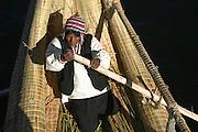 Man paddling reed canoe  Lake Titicaca, Peru