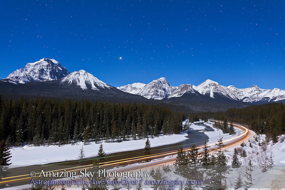 A moonlit nightscape shot from February 2012, with a gibbous Moon providing illumination over the Bow River and Morant's Curve in Banff. Venus is the bright obect over the Lake Louise range mountains. A 30-second exposure at f/2.8 and ISO 400 with the Canon 5D MkII and Canon L-series 24mm lens. This version is with the back of the train going through the scene leaving a trail of light round the curve of the railway.