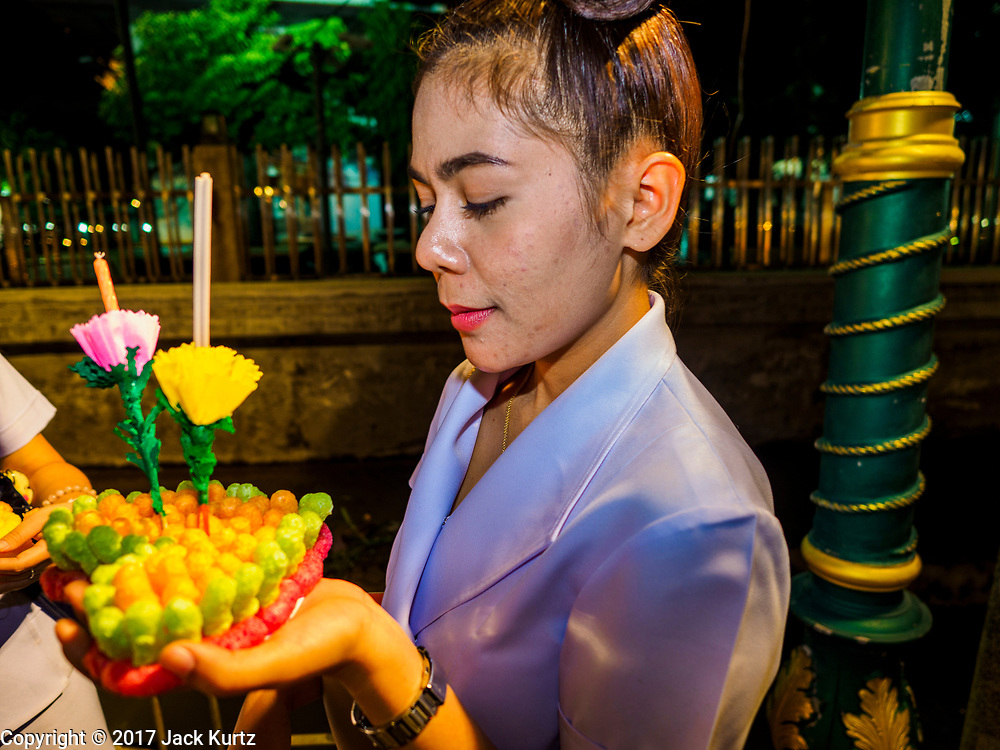 "03 NOVEMBER 2017 - BANGKOK, THAILAND:  A woman prays before floating her krathong during Loi Krathong at Wat Prayurawongsawat on the Thonburi side of the Chao Phraya River. Loi Krathong is translated as ""to float (Loi) a basket (Krathong)"", and comes from the tradition of making krathong or buoyant, decorated baskets, which are then floated on a river to make merit. On the night of the full moon of the 12th lunar month (usually November), Thais launch their krathong on a river, canal or a pond, making a wish as they do so. Loi Krathong is also celebrated in other Theravada Buddhist countries like Myanmar, where it is called the Tazaungdaing Festival, and Cambodia, where it is called Bon Om Tuk.    PHOTO BY JACK KURTZ"