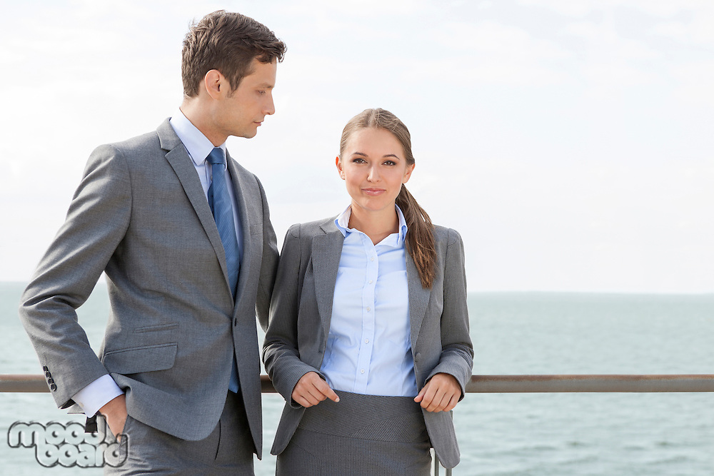 Portrait of businesswoman with coworker leaning on terrace railing against sky