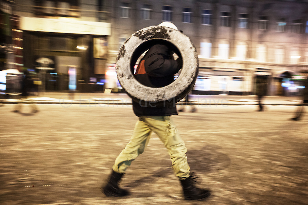 Anti government protesters arrive on Hrushevskoho street with tires to reinforce the barricades  in Kiev, 23 January 2014.