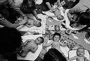 """The week of Dunblane.""  Mindful of the Dunblane massacre that week, a baby massage class takes place at a health clinic in south London. Spread across a matt are six babies of varying ages and sizes whose mums are tenderly stroking their infants' bodies and senses with soft, gentle touches over the head, face, shoulders, arms, chest, stomach and legs which is a recommended way of tactile communication between mother and child. Some children are looking up into their mothers' faces, others are looking elsewhere and one is upset but comforted. This is from a documentary series of pictures about the first year of the photographer's first child Ella. Accompanied by personal reflections and references from various nursery rhymes, this work describes his wife Lynda's journey from expectant to actual motherhood and for Ella - from new-born to one year-old..."