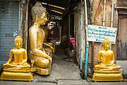 "12 NOVEMBER 2012 - BANGKOK, THAILAND:   Statues of the Buddha for sale on Bamrung Muang Street in Bangkok. Thanon Bamrung Muang (Thanon is Thai for Road or Street) is Bangkok's ""Street of Many Buddhas."" Like many ancient cities, Bangkok was once a city of artisan's neighborhoods and Bamrung Muang Road, near Bangkok's present day city hall, was once the street where all the country's Buddha statues were made. Now they made in factories on the edge of Bangkok, but Bamrung Muang Road is still where the statues are sold. Once an elephant trail, it was one of the first streets paved in Bangkok. It is the largest center of Buddhist supplies in Thailand. Not just statues but also monk's robes, candles, alms bowls, and pre-configured alms baskets are for sale along both sides of the street.    PHOTO BY JACK KURTZ"