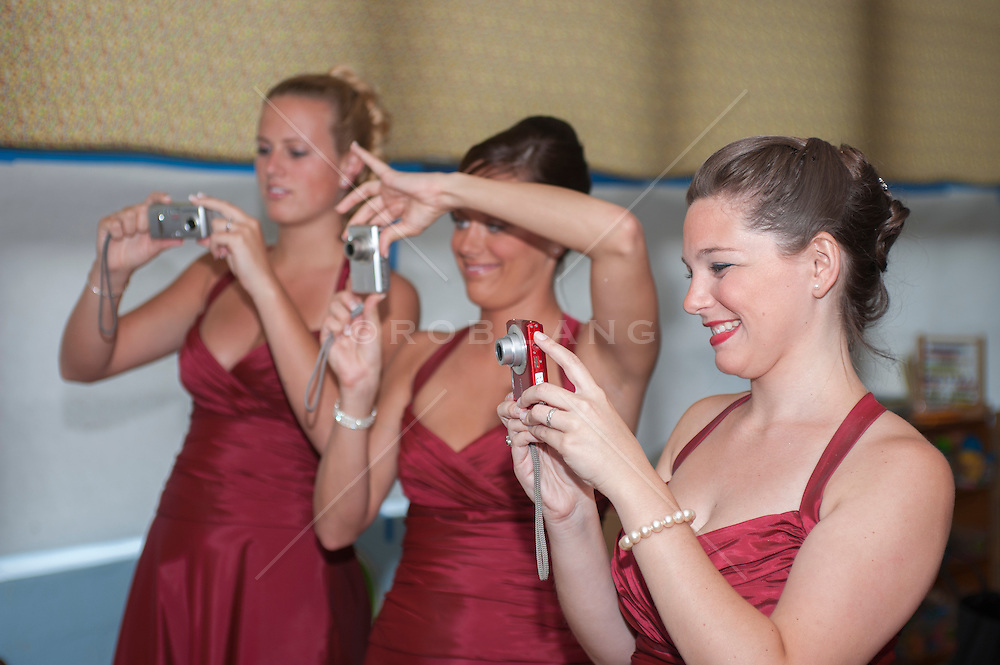 three bridesmaids taking photographs