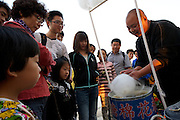 A cotton candy vendor uses his mobile bike-vending-station to sell his sugary goodness--much to the delight of Chinese tourists.  2011 Tour of Beijing