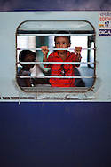 Young boy at the window of a train before train departs at New Delhi Train Station, Delhi, India