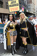 "A transgendered couple wear elaborate costumes somewhat similar to those of Wonder Womanand Superwoman. They carry a sign that reads ""Just Married Together 15 years!"""