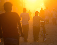 Busy street scene at sunset with silhouettes of people and bicycles, Nepalganj, Nepal