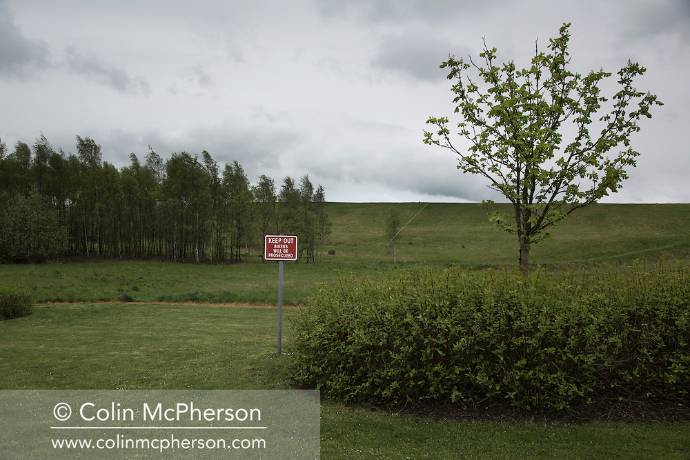 'Untitled, 2014' from the project 'The Fall and Rise of Ravenscraig' by photographer Colin McPherson.<br /> <br /> The photograph shows a warning sign on the site of the former Ravenscraig steelworks. <br /> <br /> This project, photographed in 2014, looks at the topography of the post-industrial landscape at Ravenscraig, the site until its closure in 1992 of the largest hot strip steel mill in western Europe. In its current state, Ravenscraig is one of the largest derelict sites in Europe measuring over 1,125 acres (4.55 km2) in size, an area equivalent to 700 football pitches or twice the size of Monaco. It is currently being developed with a mix of housing, retail and the home of South Lanarkshire College and the Ravenscraig Regional Sports Facility.
