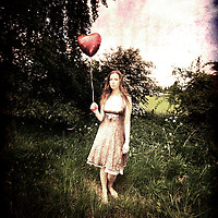 A young girl in a field with a red ballon shaped like a heart, wearing a white dress.