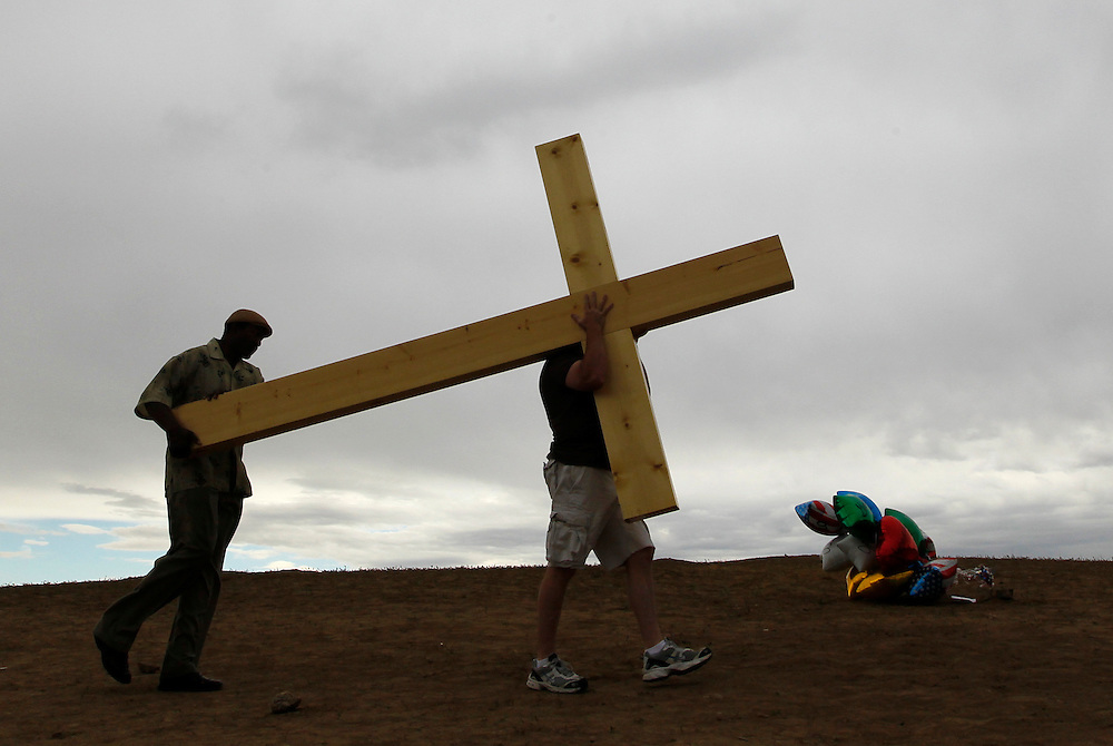 Man arrive with a large cross to be placed at a memorial to those killed in Aurora, Colorado July 28, 2012. Four more funerals for victims were held today across the country.  REUTERS/Rick Wilking (UNITED STATES)
